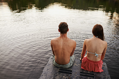 Buy stock photo Rear view shot of two teenagers sitting on the end of a pier on a lake