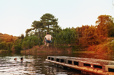 Buy stock photo Shot of a teenage boy jumping off a pier into a lake where his friends are swimming