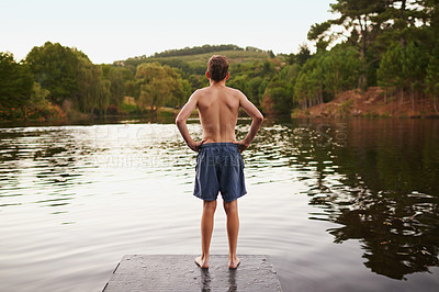 Buy stock photo A young boy standing on a jetty and looking out onto a dam