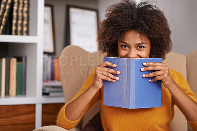 Buy stock photo Portrait of an attractive young woman peering over the book she's reading