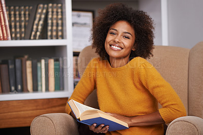 Buy stock photo Portrait of an attractive young woman reading a book