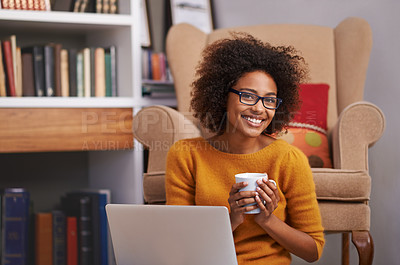 Buy stock photo Portrait of an attractive young woman drinking coffee while working on her laptop