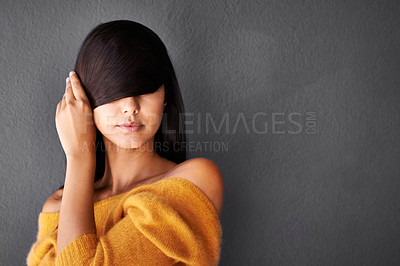 Buy stock photo Closeup shot of an attractive young woman covering her eyes with her hair