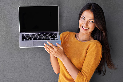 Buy stock photo Shot of a beautiful woman presenting a blank laptop screen against a gray background