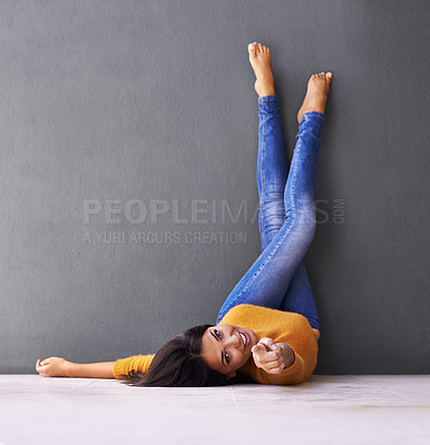 Buy stock photo A young woman pointing at the camera while lying on the floor with her feet against the wall