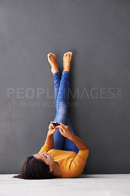 Buy stock photo A young woman using a mobile phone while lying on the floor with her feet against the wall