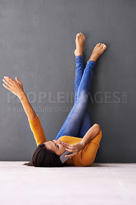Buy stock photo A young woman talking on the phone while lying on the floor with her feet against the wall