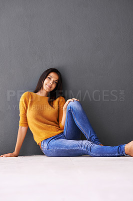 Buy stock photo An attractive young woman sitting on the floor and leaning against a gray wall