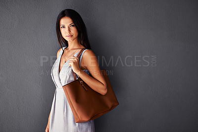Buy stock photo Studio portrait of an attractive young woman holding her handbag
