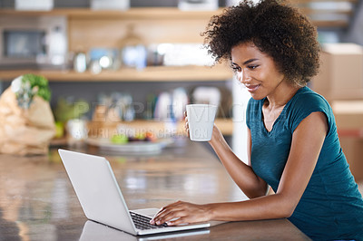 Buy stock photo Young woman using a laptop while drinking from a mug