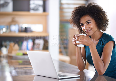 Buy stock photo Cropped shot of an attractive young woman drinking coffee and using her laptop