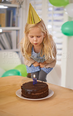 Buy stock photo Shot of a young girl blowing out the candle on her birthday cake