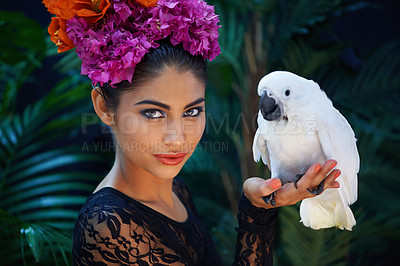Buy stock photo Shot of an exotic looking woman with a parrot perched on her hand