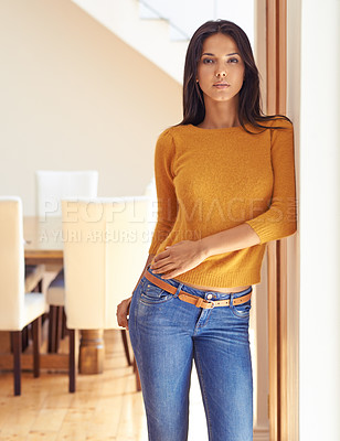 Buy stock photo Portrait of an attractive young woman leaning against a door frame
