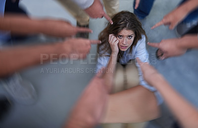 Buy stock photo Shot of a fearful young woman trying to hide from her coworkers' accusatory fingers