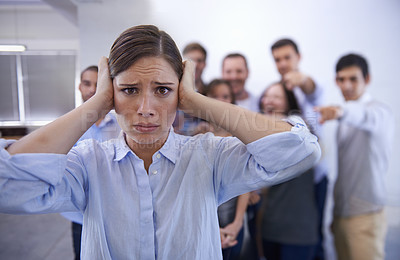 Buy stock photo Shot of a stressed young woman trying to block out her coworkers' taunts