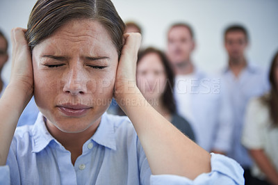 Buy stock photo Shot of a stressed young woman trying to block out the world