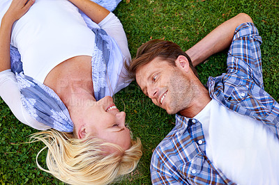 Buy stock photo High angle shot of an attractive couple lying outdoors on the grass