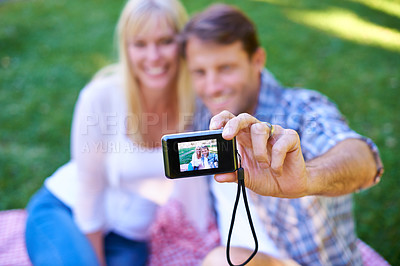 Buy stock photo Cropped shot of an attractive couple taking a selfie in the park