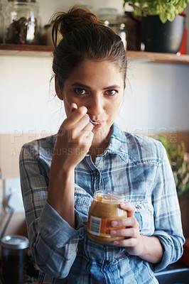 Buy stock photo Shot of a beautiful young woman eating peanut butter out of the jar with a spoon