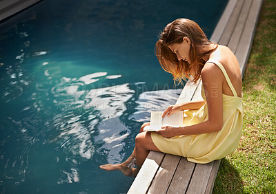 Buy stock photo An attractive young woman reading her book while resting her feet in the pool