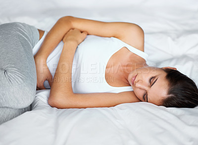 Buy stock photo A young woman lying in bed with cramps