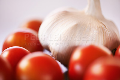 Buy stock photo A cropped shot of garlic and tomatoes on a kitchen counter