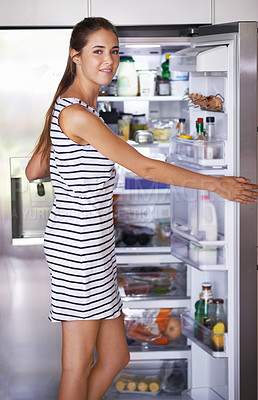 Buy stock photo Woman showing refrigerator in her kitchen