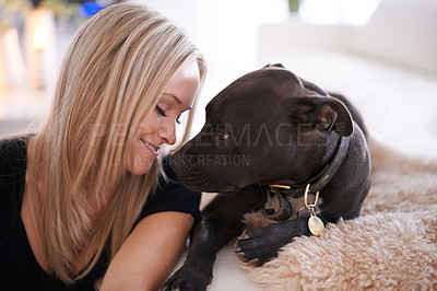 Buy stock photo Shot of a young woman at home with her dog