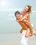 Handsome young man carrying his cute young girlfriend on his back at a beach