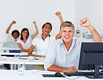 Excited business colleagues at work with their hands raised