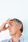 Closeup of a tensed mature man having a headache over a white background