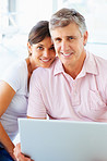 Cute mature couple working on a laptop at home