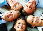 Happy business team lying down on the floor in a circle