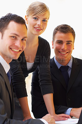 Buy stock photo Portrait of a group of corporate businesspeople talking together over paperwork