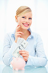 Happy woman holding cash with piggybank on table