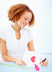 Beautiful smiling woman writing on valentines card