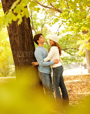 Buy stock photo Young beautiful couple standing by a tree and hugging each other