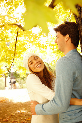 Buy stock photo Sweet young couple standing under a tree and hugging each other out in the woods