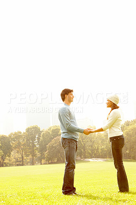 Buy stock photo Young couple  holding hands in a field
