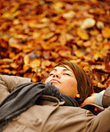 Autumn - Smiling woman lying peacefully on leaves