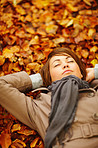 Pretty woman lying down on autumn leaves