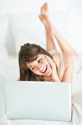 Buy stock photo Happy young woman using a laptop at home