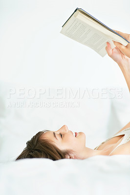 Buy stock photo Relaxed young lady reading a novel