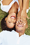 Romantic young couple having fun while lying on grass
