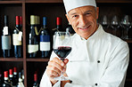 Cook holding glass of red wine