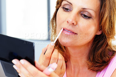Buy stock photo Pretty young woman applying cosmetics on her lips