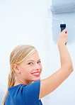 Pretty woman with the roller painting a wall