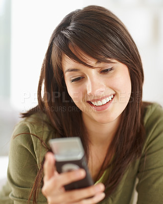 Buy stock photo Happy young female reading a text message