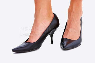 Buy stock photo Closeup of a woman's legs wearing a high heeled black shoes isolated on white background